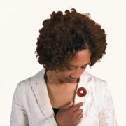 Vrouw draagt een jaspis rouwknoop als broche op een wit jasje.